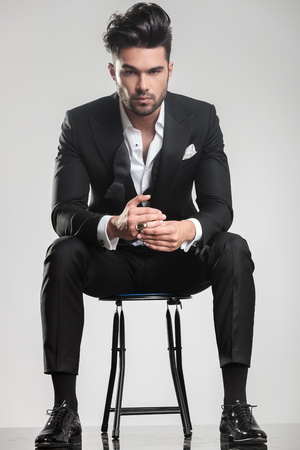 Handsome young man in tuxedo sitting on a stool while looking at the camera, holding one finger.