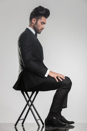 Side view of an elegant young man sitting on a stool looking down. On grey studio brackground. photo