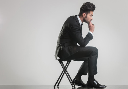 Side view of an elegant young man sitting on a stool and thinking while holding one hand to his chin.