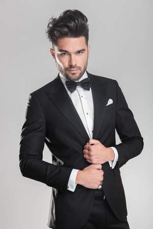 Close up of an elegant young man ajusting his tuxedo while looking at the camera photo