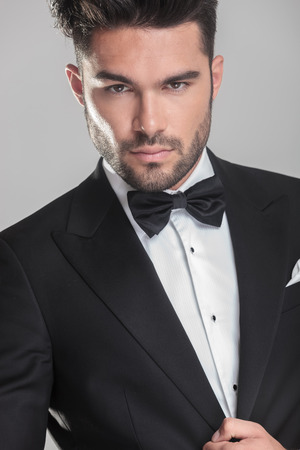 Close up picture of an handsome young man in tuxedo ajusting his jacket, lokking at the camera. On grey background.