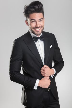 Happy young man wearing a tuxedo smiling for the camera while ajusting his jacket. on a grey background. photo