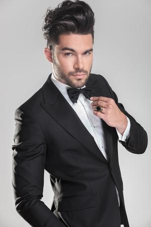 suit: Apuesto joven en smoking ajusting su pajarita mientras mira a la cámara
