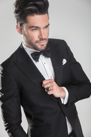 latin man: Angle view of an elegant young man ajusting his tuxedo, looking away from the camera. Stock Photo