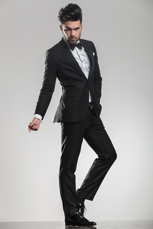 Elegant young man in tuxedo looking at the camera while snapping his finger, full body image. photo