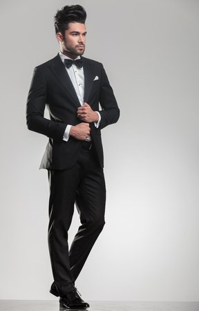Full length image of a handsome elegant man in tuxedo looking away from the camera while ajusting his jacket. photo