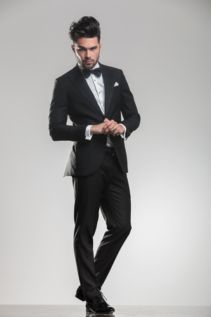groom: Full body picture of a elegant young man wearing a tudexo looking at the camera while holding his hands, Stock Photo