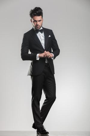 Ganzkörper-Bild von einem eleganten jungen Mann in einem tudexo schaut in die Kamera, während seine Hände halten,