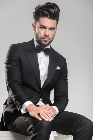 Attractive young man wearing tuxedo sitting and holding one hand onhis knee, looking at the camera. photo