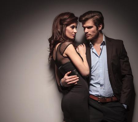 elegant woman: Elegante pareja abraz�ndose y mirando el uno al otro. El hombre es la celebraci�n de una mano en el pocketOn fondo gris oscuro. Foto de archivo