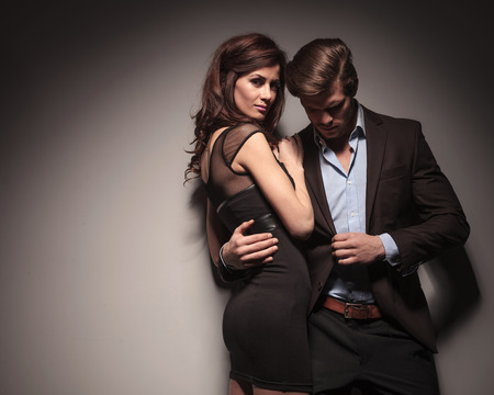Side view of a elegant woman wearing a black dress embracing her boyfriend while he is leaning on the wall holding his jacket with one hand. photo