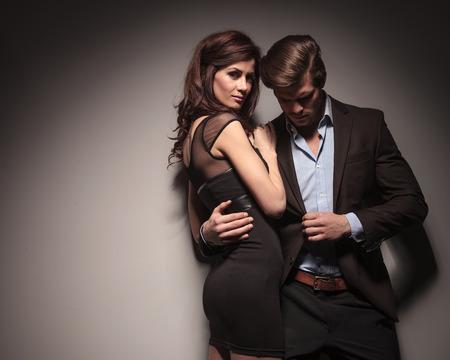pareja apasionada: Vista lateral de una mujer elegante con un vestido negro que abraza a su novio mientras �l se apoyaba en la pared celebraci�n de su chaqueta con una mano. Foto de archivo