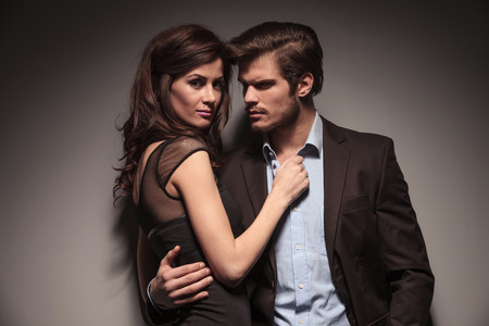 pareja apasionada: Cierre de imagen de una pareja abrazada, la mujer est� mirando a la c�mara mientras que el hombre est� mirando a otro lado. Sobre fondo gris oscuro.