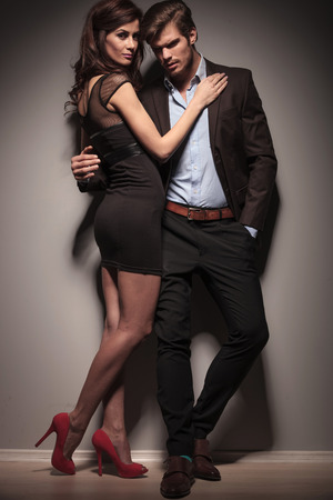 two girls hugging: Fulll length picture of a elegant couple embracing. The man is leaning on a dark grey wall with one hand in his pocket.