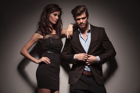Picture of a elegant fashion couple, the man is unbuttoning his jacket while the woman is looking at him and leaning with one arm. On dark grey background. photo