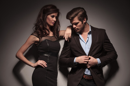 both: Elegant woman wearing a black dress looking and leaning on her boyfriend while the man is unbuttoning his brown jacket. Both looking away from the camera.