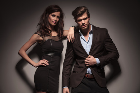 lean on hands: Portrait of a elegant couple leaning on a dark grey wall, the woman wearing a black dress is leaning on the man while the man is unbuttoning his jacket.