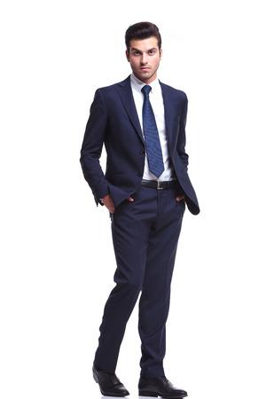 suit: Foto de cuerpo entero de un hombre de negocios elegante caminar con las manos en el bolsillo, mirando a la cámara, sobre fondo blanco