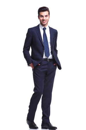 Handsome business man holding his hands in pocket while walking on white studio background, looking at the camera photo