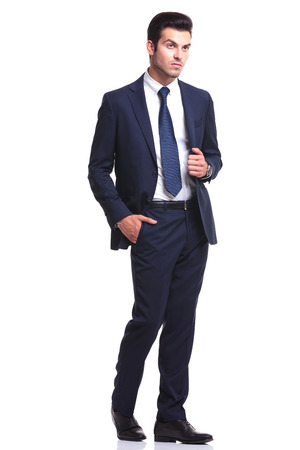 white body suit: Elegant business man walking on white studio background, with one hand in his pocket and the other one on his jacket, looking away from the camera Stock Photo