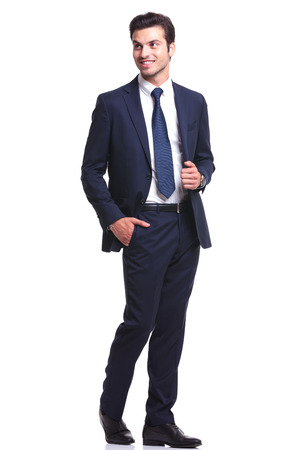 full length picture of a young business man walking while holding his hand in pocket, looking away from the camera, on white background