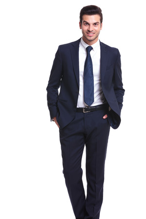 Picture of a handsome business man smiling to the camera while holding his hands in pocket Stock fotó
