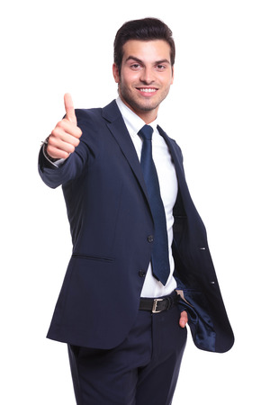 young business man showing thumb up and holding the other hand in his pocket, while smiling to the camera on white background photo