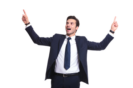 handsome business man enjoying his success, holding both hands up and screaming photo