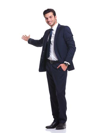Zijaanzicht van een gelukkig zaken man u te verwelkomen met een hand in zijn zak terwijl het glimlachen, op witte achtergrond