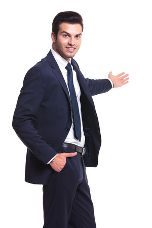 Successful business man presenting something and holding one hand in his pocket while looking at the camera, on white background