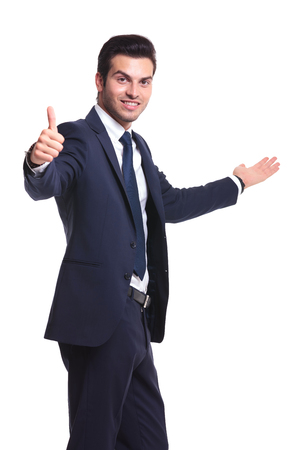 Elegant business man presenting something and showing thumbs up, while smiling to the camera Stock Photo