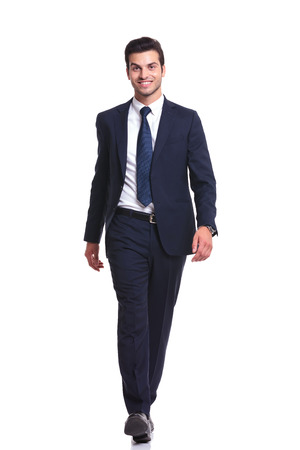 Happy business man walking on white studio background, smiling to the camera