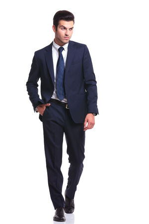 Attractive business man walking on white studio background, looking away from the camera with one hand in his pocket photo