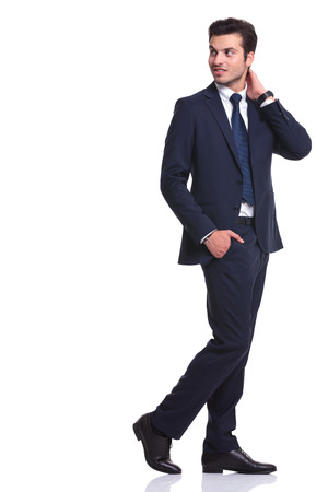Side view of a elegant business man walking on white background with one hand in his pocket and the other one to his neck, looking away from the camera photo