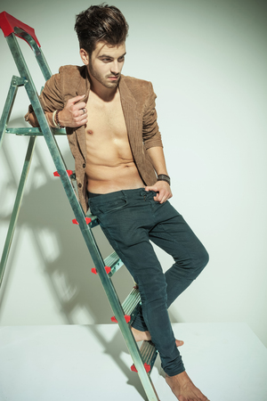 Full length picture of a handsome fashion man leaning to a ladder, looking away from the camera photo