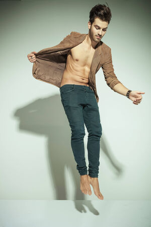 Fashion man jumping against grey background, pulling his jacket while looking down photo