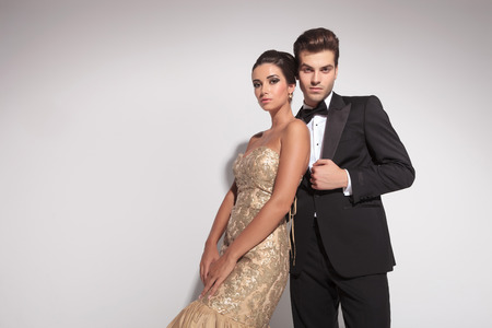 Elegant fashion couple posing against grey background, both looking at the camera.