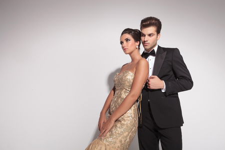 Elegant woman wearing a golden dress leaning on her lover, both looking away. On grey studion background. photo