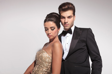 elegant business man: Close up of an elegant couple posing on grey studio background, the woman is leaning on her lover looking down, while he is looking at the camera.