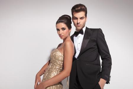 Elegant woman wearing a golden dress leaning on her lover while he is embracing her, both looking at the camera. On grey background.