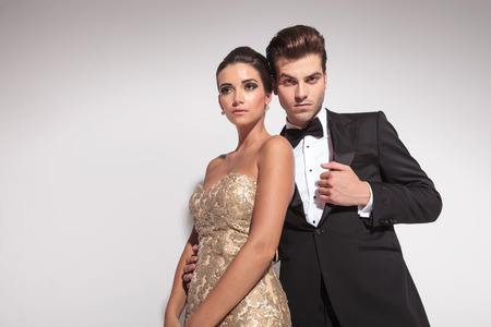 회색 스튜디오 배경에 포즈 우아한 패션 커플, 우아한 드레스를 입고 여자는 그녀의 애인에 기울고있다.