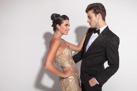 Элегантная мода пара, охватывающей, мужчина держит одну руку в кармане. Глядя друг на друга.