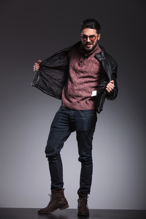 body image: Young handsome man pulling his black leather jacket while looking at the camera. Full body image.