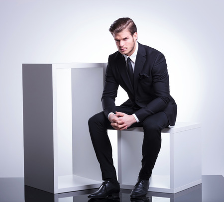 Imagen de cuerpo completo de un joven hombre de negocios sentado en un cubo blanco que sostiene la mano juntos, mirando a la cámara. Foto de archivo