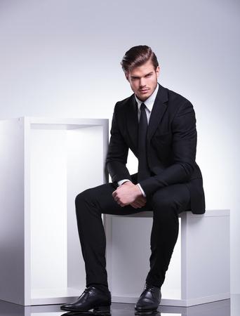 흰색 현대 의자에 앉아있는 동안 카메라를 찾고있는 매력적인 젊은 비즈니스 사람.