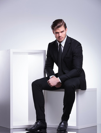 Attractive young business man looking at the camera while sitting on a white modern chair. Imagens
