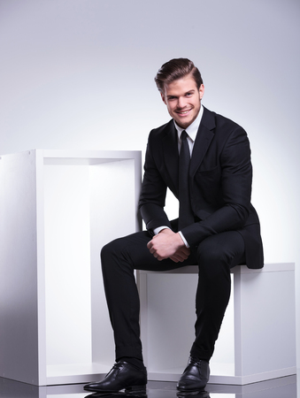 Handsome young business man smiling for the camera while sitting on a white cube. photo