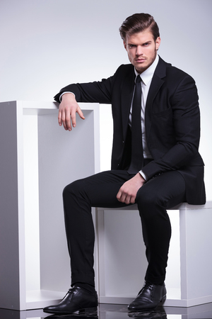 Attractive young business man sitting on a white chair while resting his hand on a table near him. Looking at the camera. photo