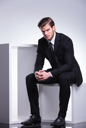 sit: Handsome business man sitting on a white table holding his hands crossed while looking at the camera. Stock Photo