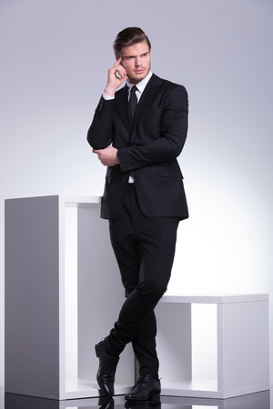 elegant business man: Attractive young business man leaning on a white modern furniture piece thinking while looking away.